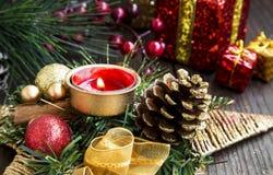 Decorazione di Natale con la candela bruciante, l'albero di abete, le palle e Ri Fotografia Stock