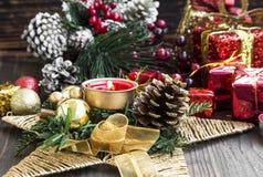 Decorazione di Natale con la candela bruciante, l'albero di abete, le palle e Ri Immagine Stock