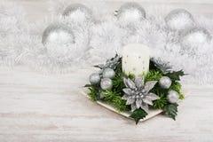Decorazione di Natale con la candela, il ramo dell'abete e le palle dell'argento su fondo di legno bianco Fotografia Stock