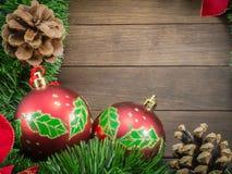 Decorazione di Natale con le bagattelle rosse su fondo di legno Fotografia Stock