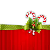 Decorazione di Natale con le foglie e la caramella dell'agrifoglio Fotografia Stock