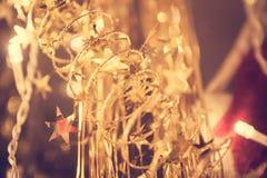 Decorazione di Natale con le stelle dorate sulla ghirlanda di natale alle luci calde Immagine Stock