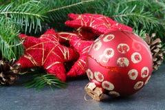 Decorazione di Natale con le stelle rosse sulla tavola con abete Fotografia Stock