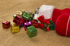 Decorazione di Natale con lo stivale del ` s di Santa ed i regali di caduta Fotografia Stock