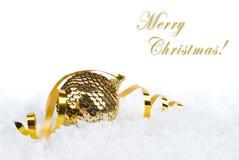 Decorazione di natale della sfera dell'oro su neve Fotografie Stock Libere da Diritti