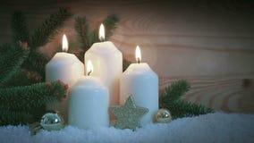 Decorazione di Natale e quattro candele brucianti di arrivo archivi video
