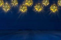 Decorazione di Natale - le stelle a forma di luci emettono luce sul fondo di legno del blu di indaco Immagini Stock Libere da Diritti
