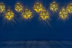 Decorazione di Natale - le stelle a forma di luci emettono luce sul fondo di legno del blu di indaco Immagini Stock