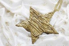 Decorazione di Natale, stella dorata sulla tovaglia Fotografia Stock Libera da Diritti
