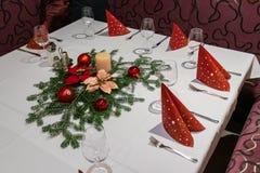 Decorazione di Natale su una tavola del ristorante vetro di vino, tovaglioli rossi; fotografia stock