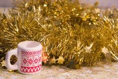 Decorazione di Natale di una ghirlanda brillante e di una tazza con un ornamento di inverno Immagine Stock Libera da Diritti