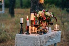 Decorazione di nozze con i vetri, i fiori, i vasi, le candele e la frutta o immagine stock libera da diritti