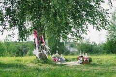 Decorazione di nozze dai fiori e dalle decorazioni con oscillazione sotto gli alberi all'aperto Immagini Stock