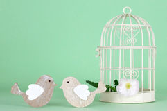 Decorazione di nozze: Due uccelli accanto alla gabbia per uccelli bianca Immagini Stock