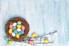 Decorazione di Pasqua Corona di Pasqua ed uova di Pasqua variopinte su fondo blu Vista superiore, spazio della copia Immagini Stock Libere da Diritti