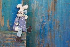 Decorazione di Pasqua nell'interno con un coniglietto su una parte posteriore di legno del blu Fotografia Stock