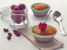 Decorazione di recente del muffin nudo con la ciliegia fresca ed asciutta Fuoco selettivo modificato Fotografia Stock Libera da Diritti