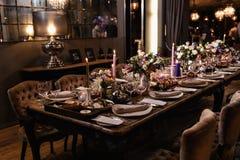 Decorazione di una tavola ad un ricevimento nuziale o ad una festa di compleanno - bei colori scuri immagine stock