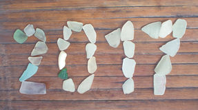 Decorazione di vetro del mare su fondo di legno Mosaico di vetro del mare da 2017 nuovi anni Fotografie Stock Libere da Diritti