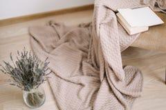 Decorazione domestica accogliente poltrona con una coperta e un libro, un vaso con un mazzo di lavanda Interior design domestico  fotografia stock