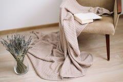 Decorazione domestica accogliente poltrona con una coperta e un libro, un vaso con un mazzo di lavanda Interior design domestico  immagini stock