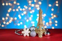 Decorazione dorata della torre Eiffel, giocattolo Natale, decorazioni del nuovo anno, ornamenti Fondo vago dorato blu del bokeh Fotografie Stock Libere da Diritti