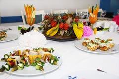 decorazione festiva della tavola con le insalate, gli spuntini e un mazzo dei fiori fotografia stock