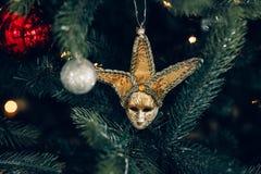 Decorazione festiva sotto forma di una maschera sexy, su un fondo dell'albero di Natale Fotografia Stock