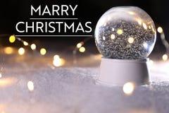Decorazione festiva sul BUON NATALE del messaggio e della neve contro fondo scuro fotografia stock
