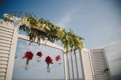 Decorazione floreale di nozze originali nella forma di mini vasi ed in mazzi dei fiori che pendono dall'altare di nozze, all'aper Immagine Stock Libera da Diritti