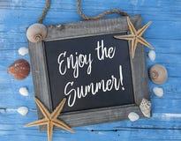 Decorazione marittima con il pesce della stella, coperture su legno stagionato blu con lo slogan godere del summe fotografia stock