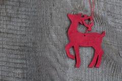Decorazione rossa di legno dei cervi di natale su fondo di legno Fotografie Stock Libere da Diritti