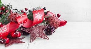Decorazione rossa di Natale con il nastro di scintillio, i coni e la stella Orn Fotografie Stock