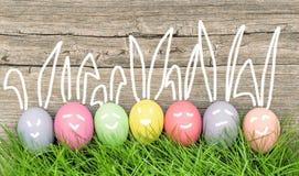 Decorazione sorridente delle uova di Pasqua dei coniglietti divertenti Fotografie Stock