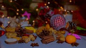 Decorazione sulla tavola - giocattoli, mandarini, biscotti, spezie di Natale stock footage