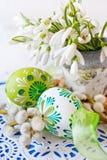 Decorazione tradizionale di Ceco pasqua - vaso da fiori con i fiori di bucaneve e le uova verdi decorate con i pussycats Immagine Stock