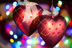 Decorazioni del cuore dell'albero di Natale contro il fondo piacevole delle luci Carta di giorno di Natale, del nuovo anno o di b immagine stock libera da diritti