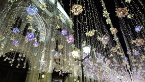 Decorazioni del nuovo anno di illuminazione di Natale, via brillante di notte in città concentrare, luci intense e palle, belle stock footage