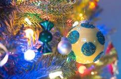 Decorazioni dell'albero di Natale Il rivestimento giallo e brillante, globo con i cerchi blu, emette luce, circondato dal multico Immagine Stock Libera da Diritti