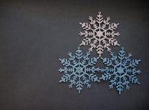 Decorazioni dell'albero di Natale tre fiocchi di neve sulla vacanza invernale grigia del fondo immagini stock libere da diritti