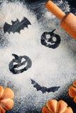 Decorazioni di Halloween del disegno sul fondo della farina, dolci sotto forma della zucca e matterello Halloween che cucina conc immagine stock libera da diritti