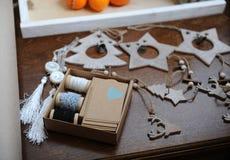 Decorazioni di legno di Natale fatte a mano Testa di un cervo, degli alberi di Natale e delle stelle Mandarini in un vassoio nei  Fotografia Stock Libera da Diritti