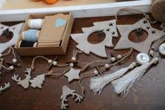 Decorazioni di legno di Natale fatte a mano Testa di un cervo, degli alberi di Natale e delle stelle Scatola di Kraft con i nastr Fotografia Stock Libera da Diritti