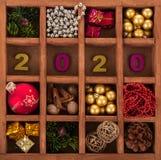 Decorazioni di Natale, regali, spezie ed urti, iscrizione 2020, in scatola di legno con le cellule Fotografie Stock