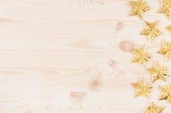 Decorazioni di Natale, stelle d'oro su fondo di legno beige molle Immagine Stock Libera da Diritti
