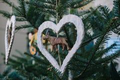 Decorazioni di Natale su un albero di Natale sotto forma di cervo di legno dentro il cuore Celebrazione del natale Immagini Stock