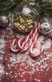Decorazioni di Natale su un fondo di legno rosso con i rami del pino ed alto vicino del bastoncino di zucchero Immagini Stock Libere da Diritti