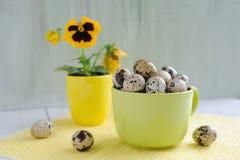 Decorazioni di Pasqua - uova, fiore e tazze sulla tavola Fotografia Stock