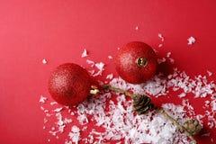 Decorazioni e neve di Natale sul contesto rosso Fotografia Stock Libera da Diritti