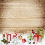 Decorazioni e regali di Natale nella neve su un fondo di legno Fotografie Stock